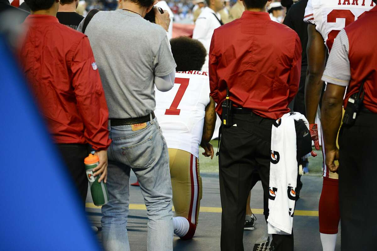 San Francisco 49ers quarterback Colin Kaepernick, middle, sits during the National Anthem before an NFL preseason football game against the San Diego Chargers, Thursday, Sept. 1, 2016, in San Diego. (AP Photo/Denis Poroy)