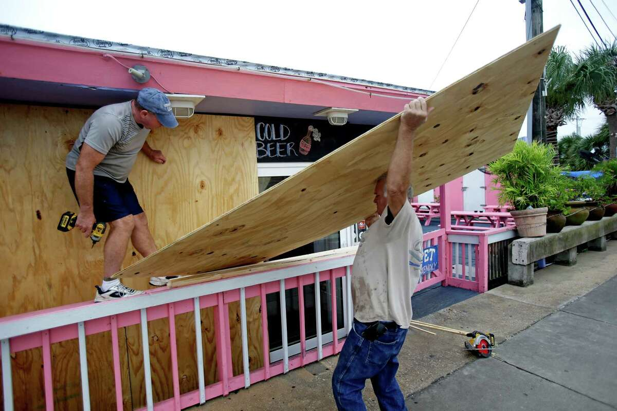 Tim Allen, left, and Joe Allen board up the front of an outdoor bar as they prepare for Tropical Storm Hermine Thursday, Sept. 1, 2016, in Cedar Key, Fla. (AP Photo/John Raoux) ORG XMIT: FLJR103