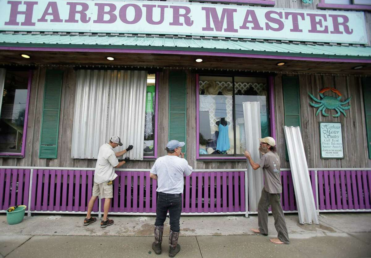 Workers install storm shutters on a store front as they prepare for Tropical Storm Hermine Thursday, Sept. 1, 2016, in Cedar Key, Fla. (AP Photo/John Raoux) ORG XMIT: FLJR106