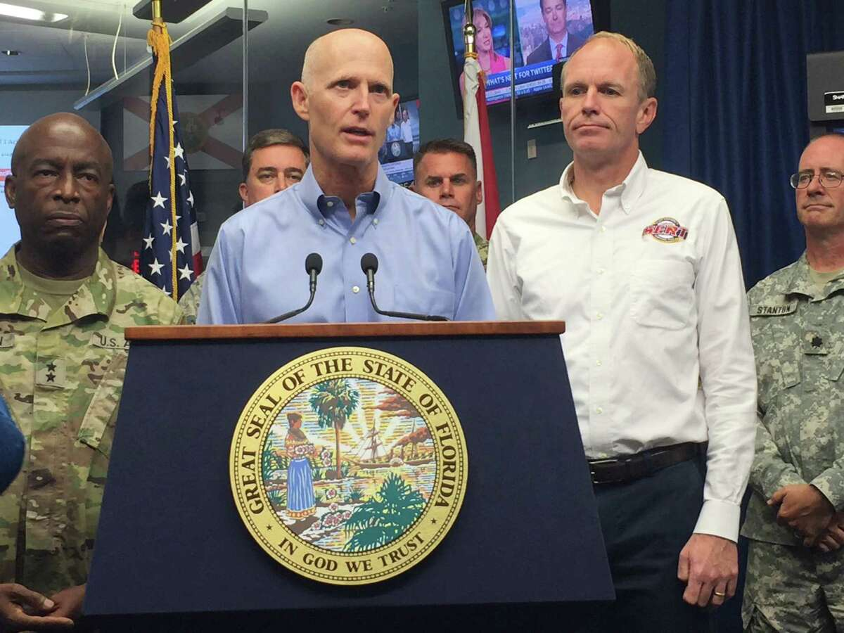 Florida Gov. Rick Scott, center, and Florida Emergency Management Director Bryan Koon, right, give an update on Tropical Storm Hermine at the State Disaster Operations Center in Tallahassee, Fla., on Thursday, Sept. 1, 2016. Scott says Tropical Storm Hermine is potentially life-threatening, and he's urging Gulf Coast residents to take precautions immediately. (AP Photo/Joe Reedy) ORG XMIT: FLJR201