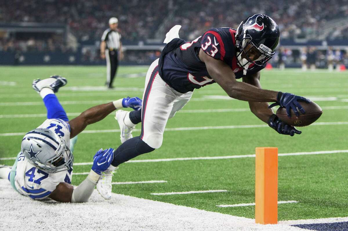 Houston Texans running back Akeem Hunt (33) reaches across the goal line with the football as he is hit by Dallas Cowboys linebacker Deon King (47) for a 10-yard touchdown reception during the third quarter of an NFL pre-season football game at AT&T Stadium on Thursday, Sept. 1, 2016, in Arlington, Texas.