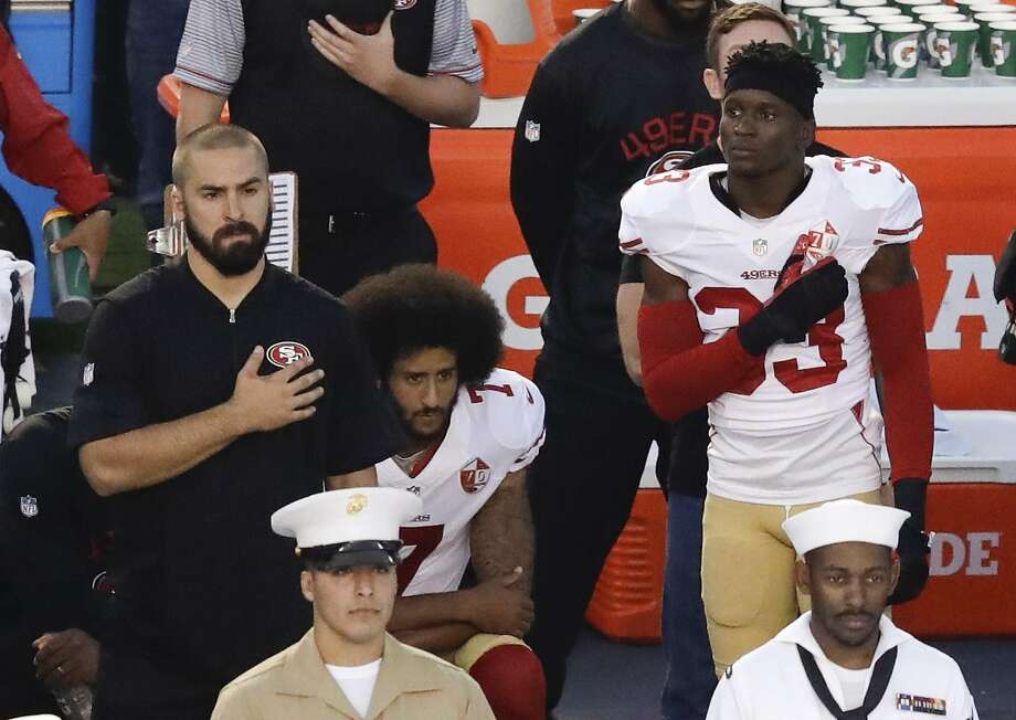 Quarterback Colin Kaepernick (center) kneels during the national anthem before the 49ers play the San Diego Chargers. Photo: Chris Carlson, Associated Press