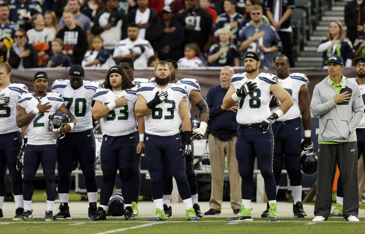 Seattle Seahawks players listen to the national anthem before a preseason NFL football game against the Oakland Raiders Thursday, Sept. 1, 2016, in Oakland, Calif. (AP Photo/Ben Margot)