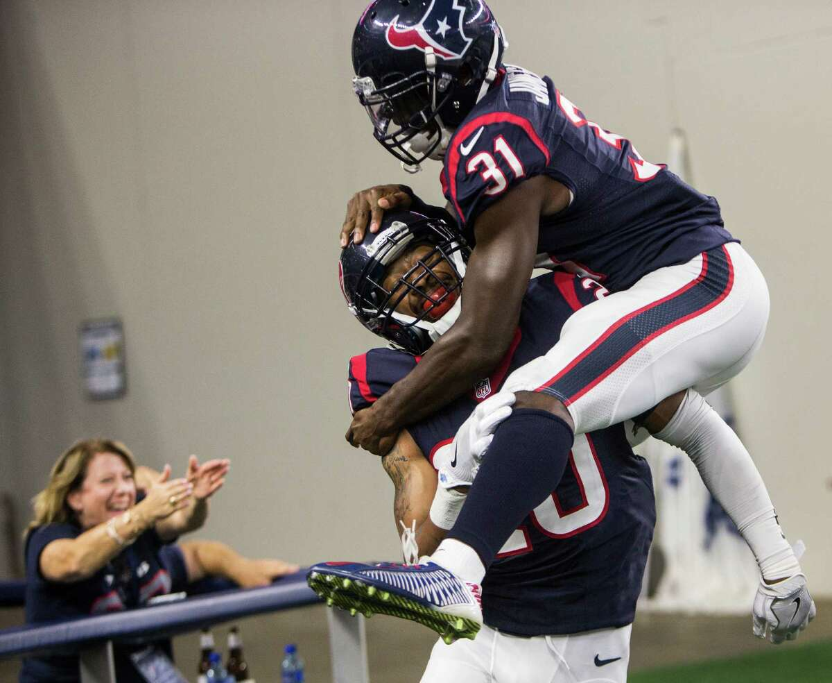 Houston Texans defensive backs Antonio Allen (20) and Charles James (31) celebrate Allen's 9-yard interception return for a touchdown against the Dallas Cowboys during the fourth quarter of an NFL pre-season football game at AT&T Stadium on Thursday, Sept. 1, 2016, in Arlington, Texas.