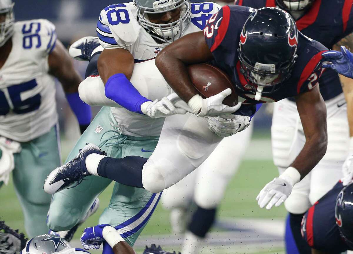 Houston Texans running back Kenny Hilliard (22) is hit by Dallas Cowboys linebacker Brandon Hepburn (48) as he dives for extra yardage during the second quarter of an NFL pre-season football game at AT&T Stadium on Thursday, Sept. 1, 2016, in Arlington, Texas.