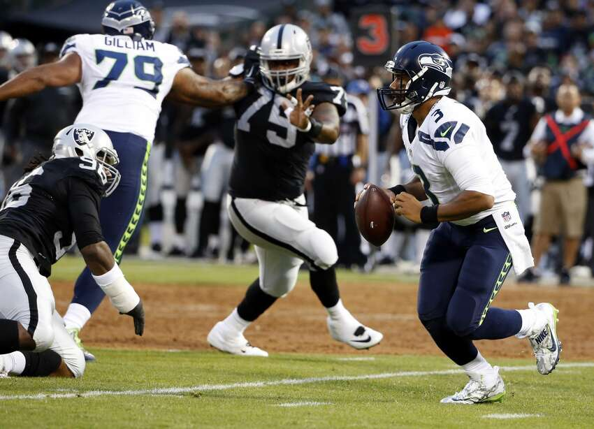 Seattle Seahawks quarterback Russell Wilson, right, runs out of the pocket against the Oakland Raiders during the first half of a preseason NFL football game Thursday, Sept. 1, 2016, in Oakland, Calif. (AP Photo/Tony Avelar)