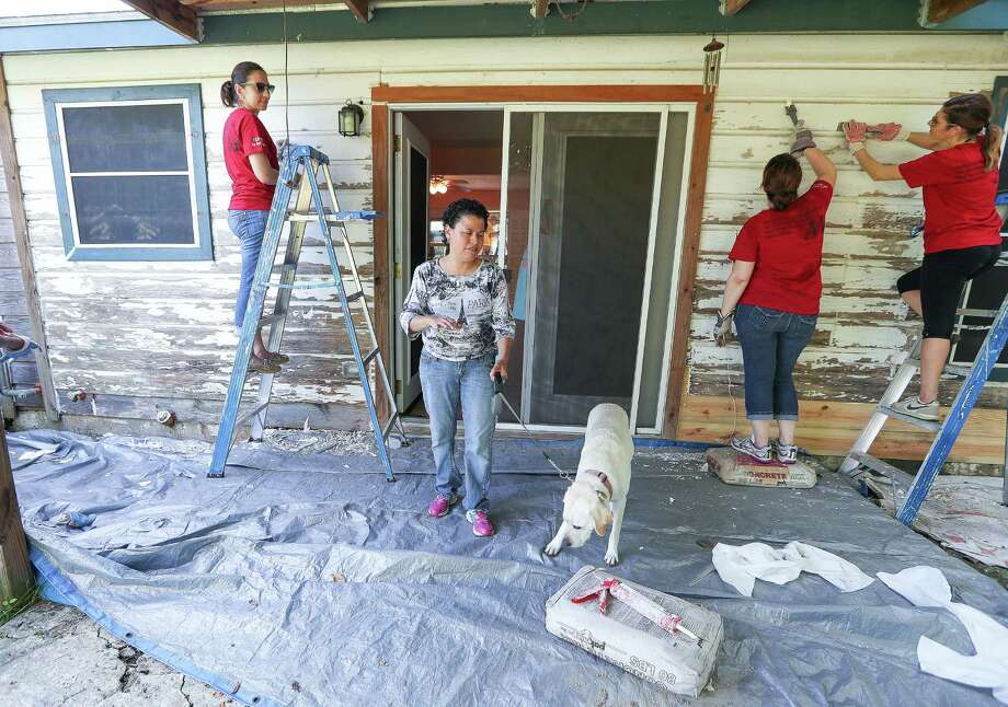 """Eva Bergara (center), who is blind, and her service dog, Kim, came outside as volunteers  worked on her home Wednesday, Aug. 31, 2016, in Houston. The crew of volunteers were part of of Methodist's I CARE IN ACTION activities on September 1.  I CARE IN ACTION volunteers from Houston Methodist Hospital will work with Rebuilding Together Houston to rehab 10 homes in five days in neighborhoods throughout the Houston area.  More than 275 employees have signed-up for the opportunity and will perform home maintenance chores such as scraping and painting exteriors, replacing damaged siding, caulking cracks and sealing any openings.  Houston MethodistÕs I CARE IN ACTION program grants eligible employees paid time to volunteer at approved community organizations to """"serve beyond our hospital walls. Rebuilding program keeps Houston's seniors safe in their homes, where many spend the majority of their time. Mitigating hazards associated with fires, falls, and poor air quality, the program provides accessibility aids to improve not only our neighbors' safety, but their independence as well. Photo: Steve Gonzales, Houston Chronicle / © 2016 Houston Chronicle"""