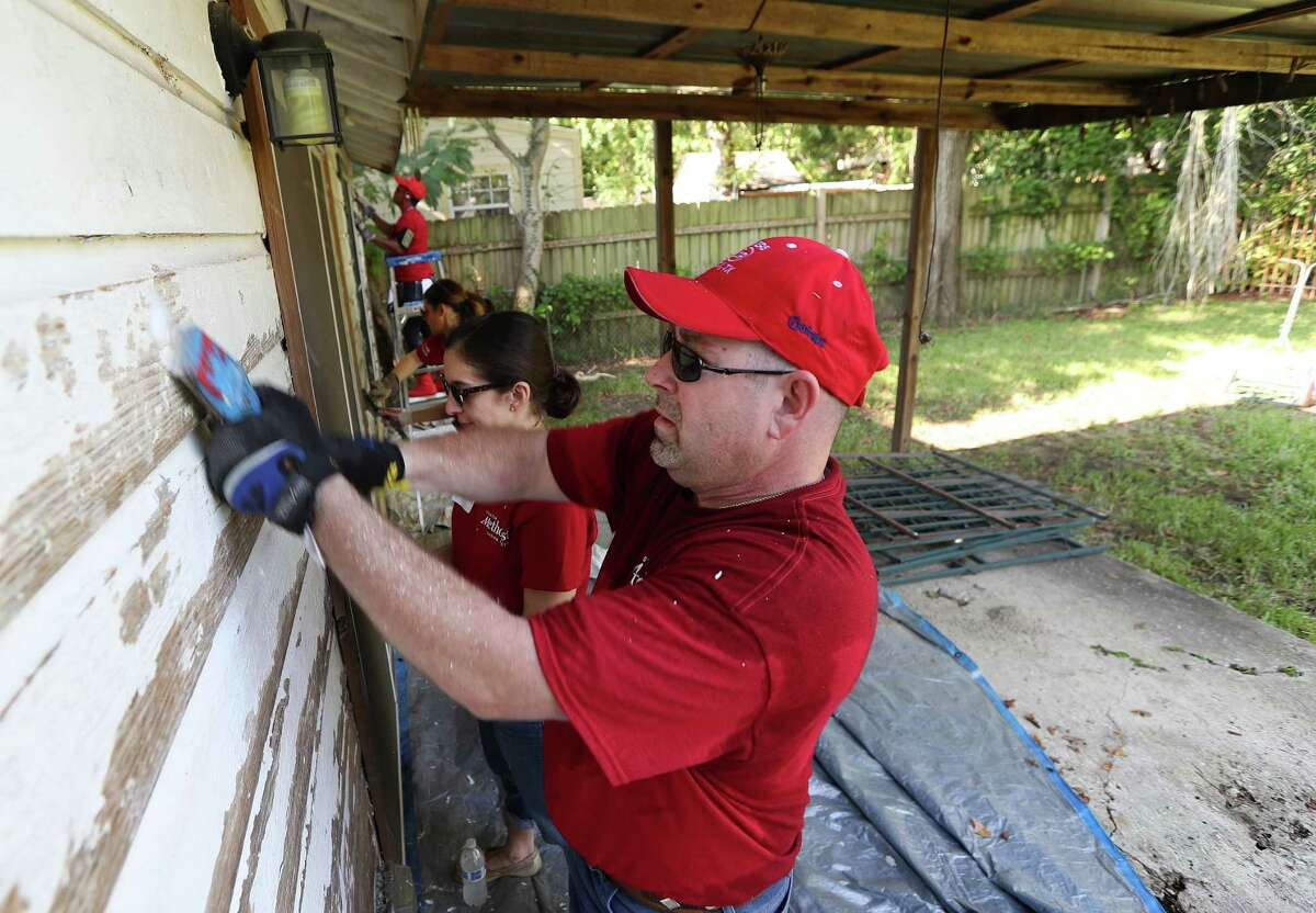 Houston Methodist Hospital's Tim Gordan and a team of other volunteers scrape paint off of Eva Bergara, who is blind, and her service dog, Kim, home Wednesday, Aug. 31, 2016, in Houston.