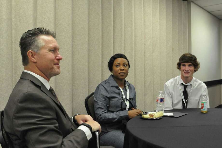 Chad Burke, CEO of the Economic Alliance Houston Port Region, meets with students Centerah Reaux and Sean Goundrey at the Pasadena Convention Center. Companies are eager to talk to young people about their career options. Photo: Chris Tomlinson