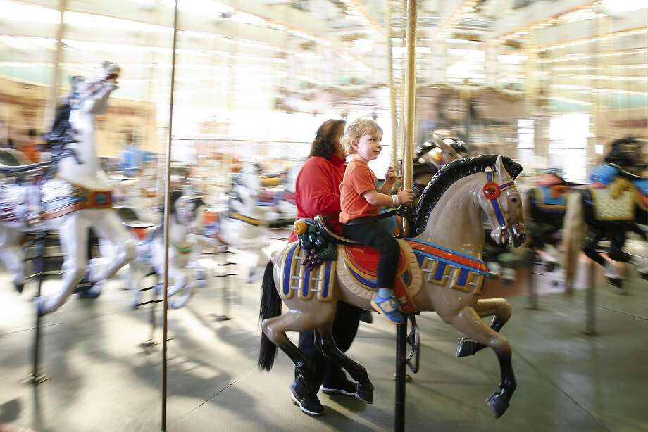 Joseph Zell, 3, and his mother, Kathy Zell, from Alameda, behind him on the carousel at the Santa Cruz Boardwalk in Santa Cruz, California on Thursday September 1, 2016. Santa Cruz Boardwalk has announced a major $12 million renovation to its main entrance, Fright Walk attraction and other rides. Photo: Craig Lee, Special To The Chronicle