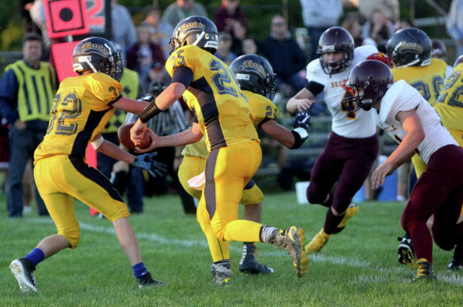 North Huron quarterback Nick Schramski (25) hands the ball off to running back Adrian Tibbits (32) in the second quarter.