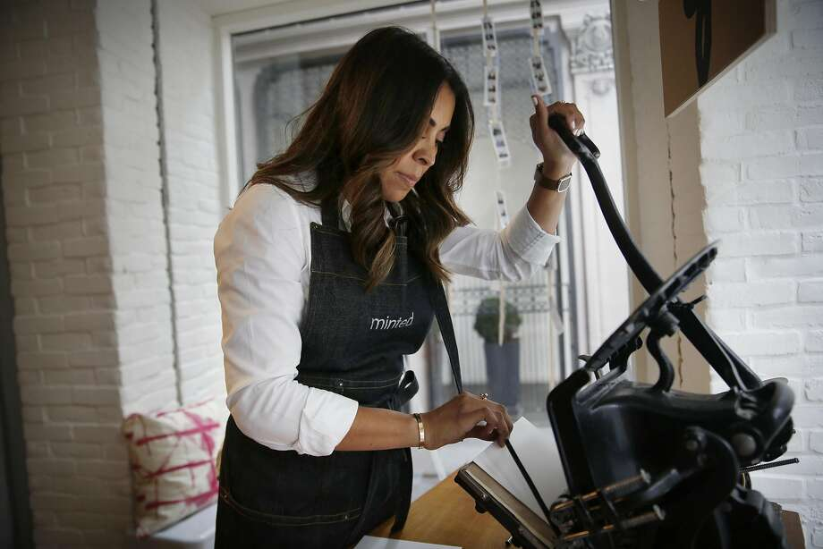 Kattya Breitenbach, manager of the Minted Local pop-up, demon strates the store's novel antique letterpress. Photo: Lea Suzuki, The Chronicle