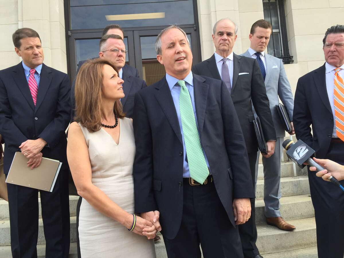 Texas Attorney General Ken Paxton, with his wife Angela, speaks briefly with reporters outside a federal courthouse in Sherman, Texas Friday Aug. 2, 2016. Paxton's attorneys tried to convince a judge to dismiss the civil charges against him.