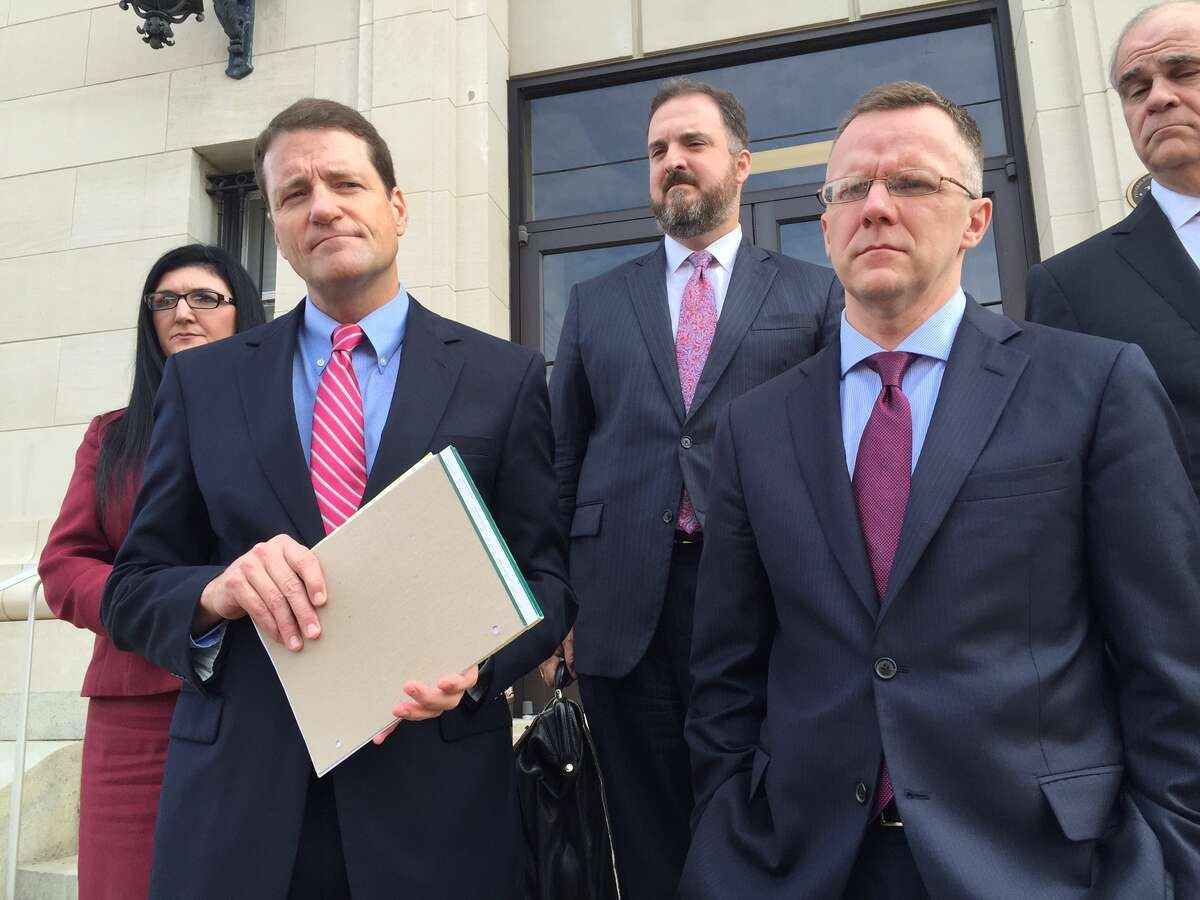 Texas Attorney General Ken Paxton's lawyers, William Mateja, left, and Matthew Martens, right, stand outside a federal courthouse following oral arguments of dismissal hearing in Sherman Friday Aug. 2, 2016. Martens argued Paxton's omission to investors he would receive a commission does not constitute securities fraud.