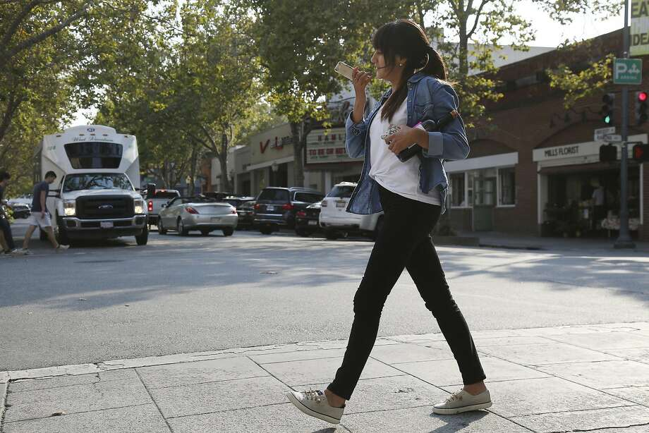 A young woman on her smartphone walks across University Avenue in downtown Palo Alto. Photo: JIM WILSON, NYT
