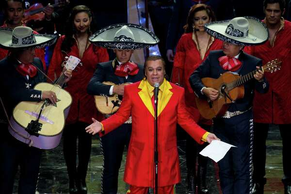 Mexican singer Juan Gabriel, front, performs during an event honoring Mexican comedian Roberto Gomez Bolanos, popularly known as Chespirito, at the National Auditorium in Mexico City. He died Aug. 28 in Santa Monica, California.