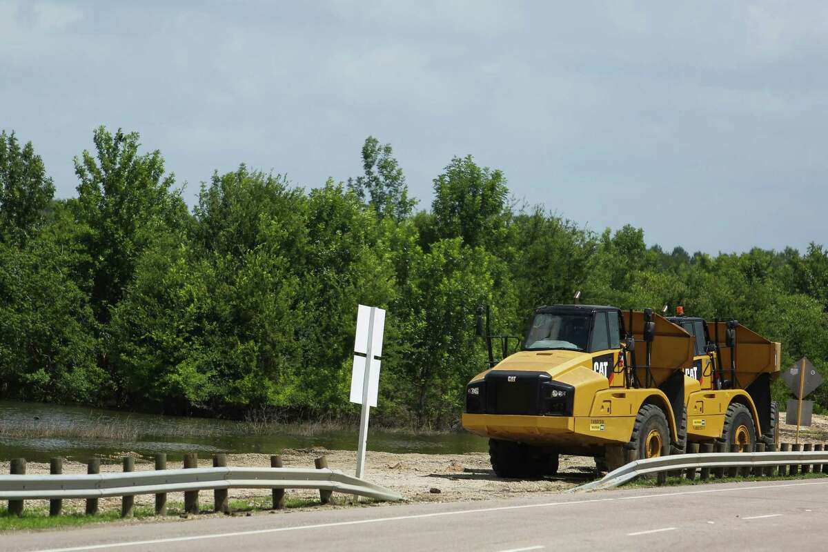 A piece of construction equipment sits next to high water in Addicks Reservoir as improvements to the dam are put on hold due to the large amount of water Tuesday, June 14, 2016 in Houston.