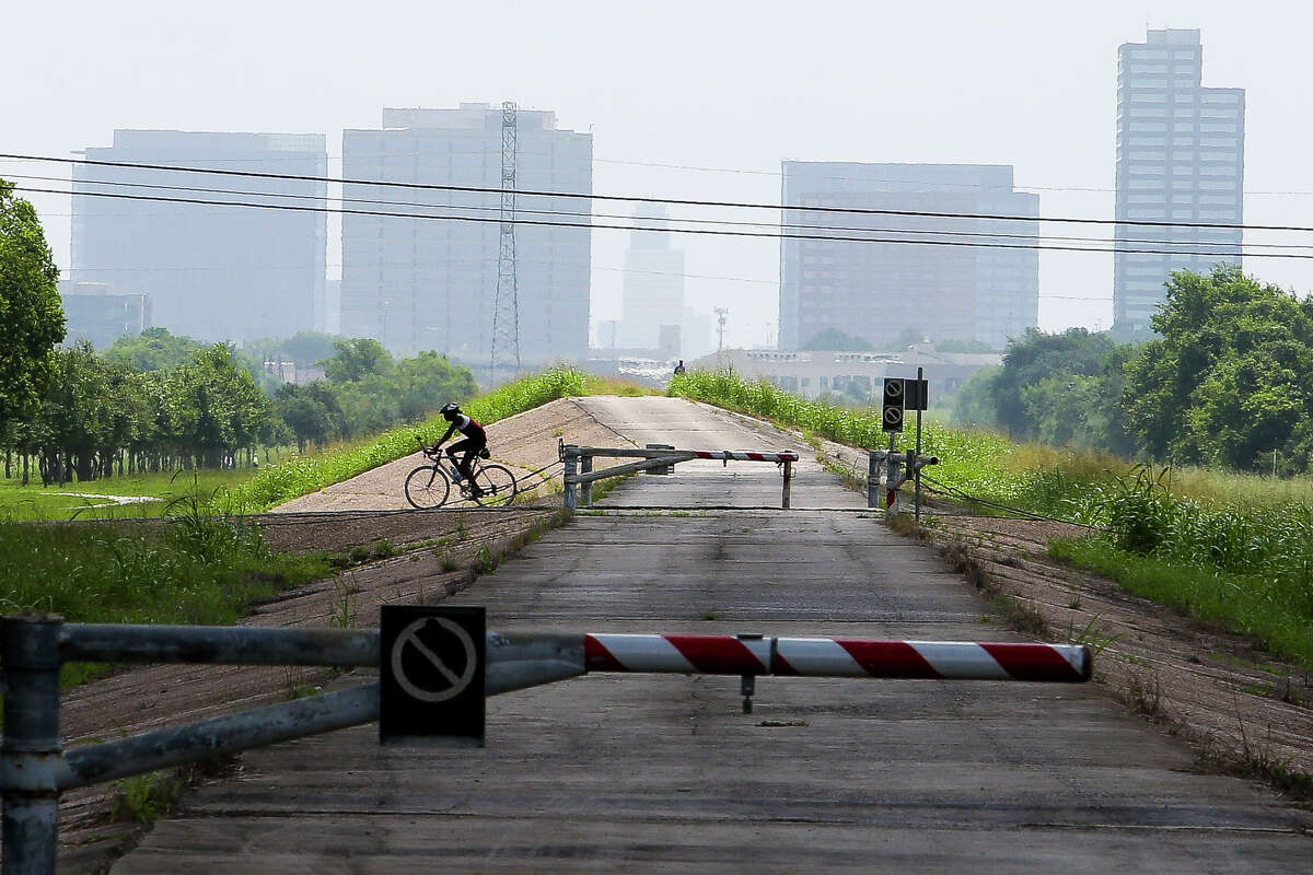 A cyclist rides over the emergency spillway of the Barker Reservoir dam Tuesday, June 14, 2016 in Houston.