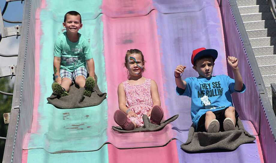 From left, Jackson Pullen of Hudson, his sister Caitlin, 6, and Gerard Martel, 10, of New Marlborough, Mass., race down a giant slide during the 176th Columbia County Fair on Friday, Sept. 2, 2016 in Chatham, N.Y.  (Lori Van Buren / Times Union) Photo: Lori Van Buren / 20037847A