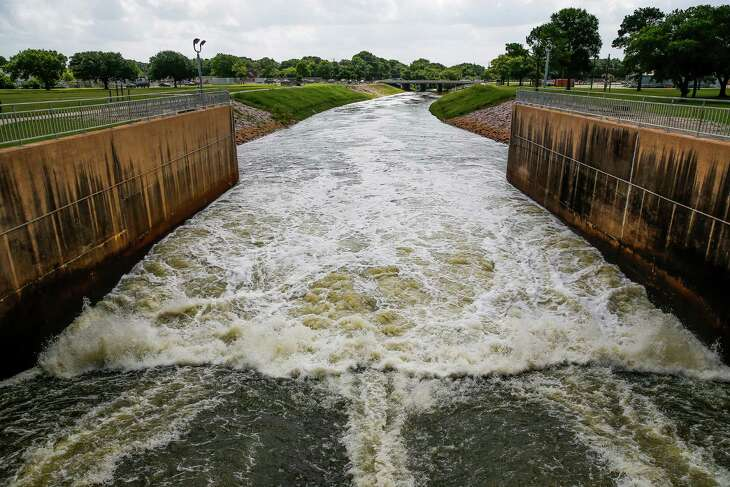 Water flows down the spillway of the Barker Reservoir dam into Buffalo Bayou, Tuesday, June 14, 2016 in Houston.