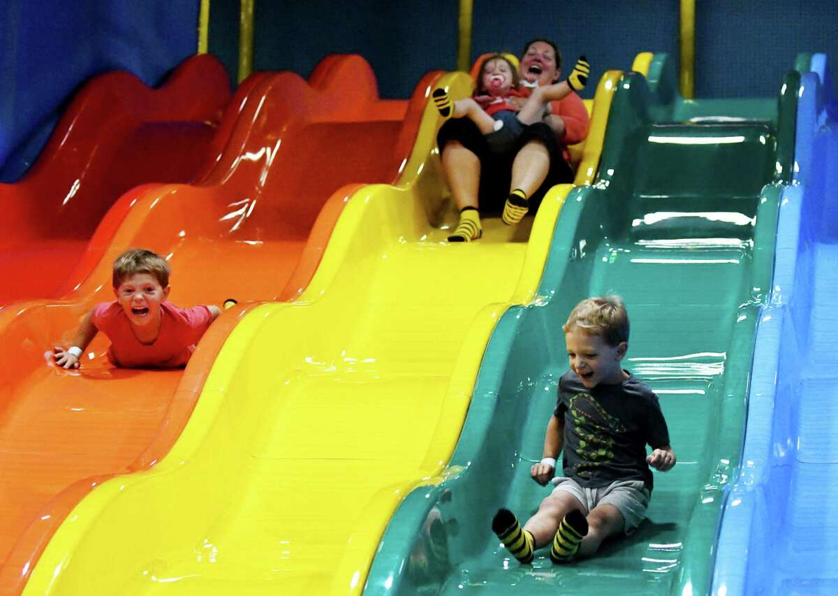Lorenzo Steinke, 6, left, mother, Celeste holding Cordelia and Xavier Steinke, 4, right of Troy enjoy one the many slides at Billy Beez in Crossgates Mall on Friday, Sept. 2, 2016, in Guilderland, N.Y. (The indoor playground is located above Best Buy. (Will Waldron/Times Union)