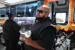 Frequent customer Carlos Molina comments on taco trucks as he grabs a bite to eat from El Tonayense taco truck on Harrison at 14th streets on Friday, September 2, 2016, in San Francisco, Calif.