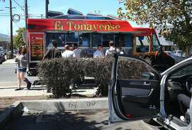 Customers grab lunch from El Tonayense taco truck on Harrison at 14th streets next to Best Buy parking lot on Friday, September 2, 2016, in San Francisco, Calif.