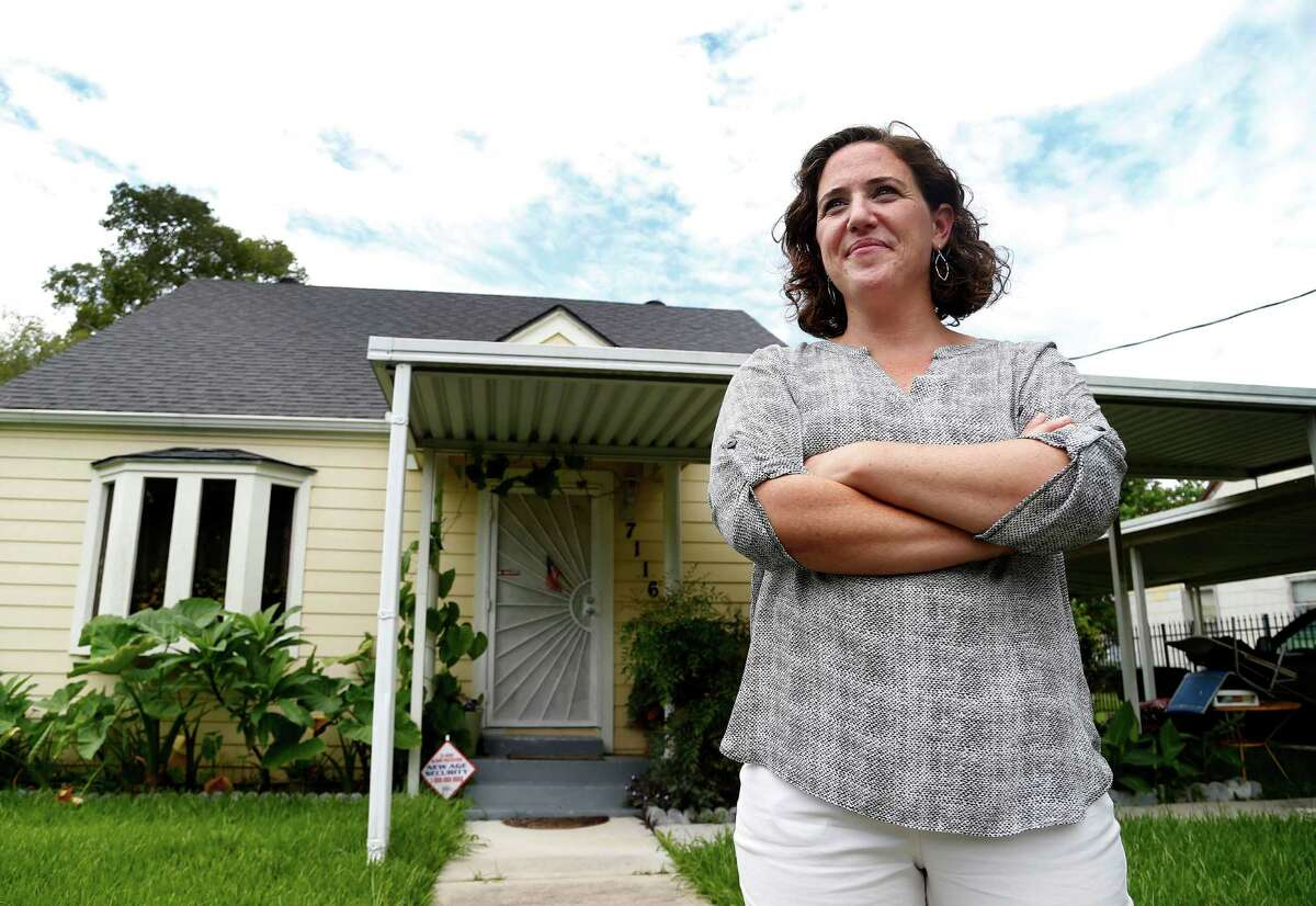 Ginny Goldman, founder of the Texas Organizing Project, stands in front of a Houston home repaired after a long battle over Hurricane Ike recovery funds.