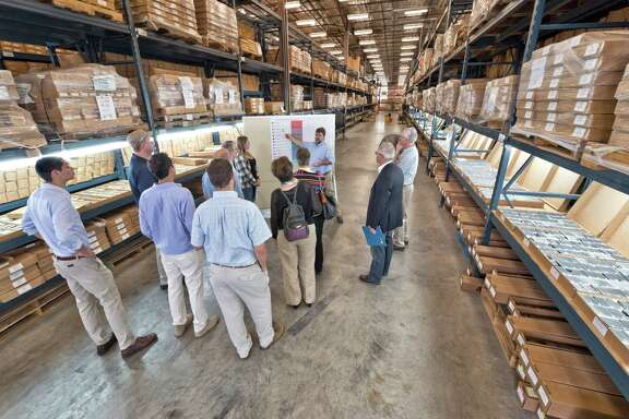 Harry Rowe, a research scientist at the University of Texas Bureau of Economic Geology, explains X-ray fluorescence technology to industry representatives in the university's oil well core sample warehouse.