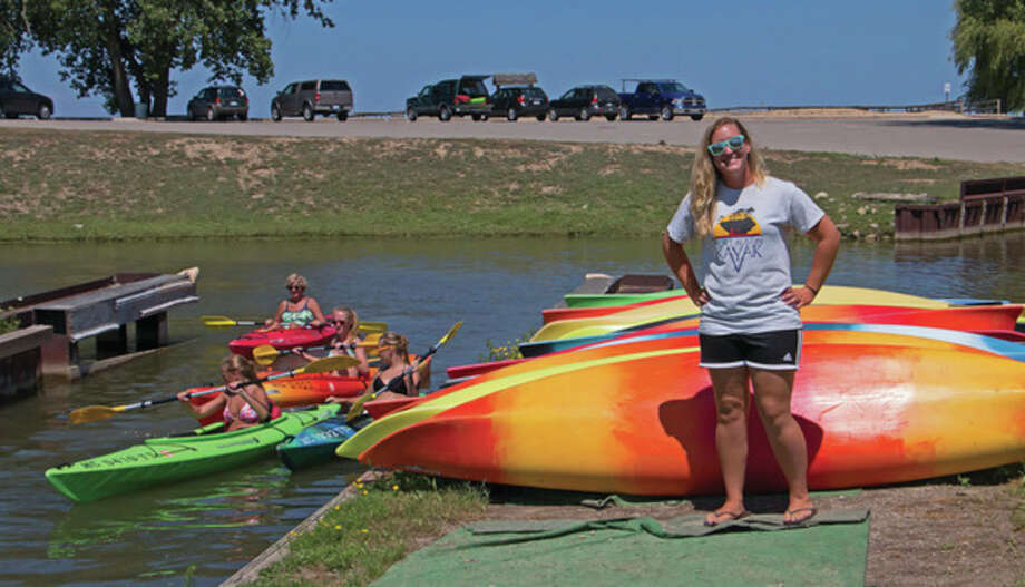 Bill Diller/For the Tribune Sarah Piotter, manager of Port Austin Kayak, stands in front of kayaks at the boat launch area of the business.