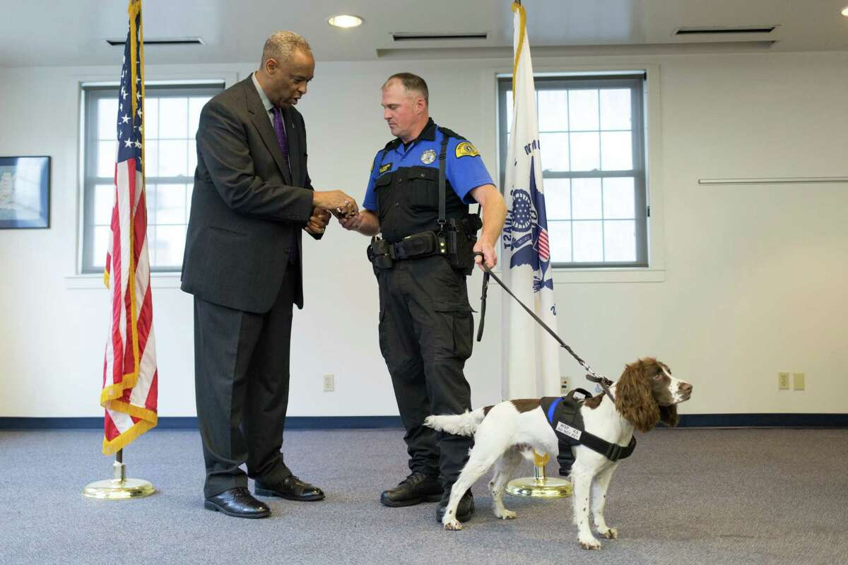 Trooper Chris Cooper and Ralph receive a badge from Washington State Patrol Chief John R. Batiste for graduating from the 20th explosive detection canine handler course at U.S. Coast Guard Base Seattle.