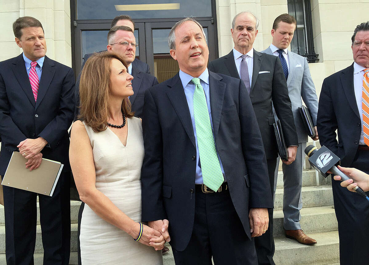 Attorney General Ken Paxton, with his wife Angela, speaks briefly with reporters outside a federal courthouse in Sherman where his attorneys tried to convince a judge to dismiss the civil charges against him.
