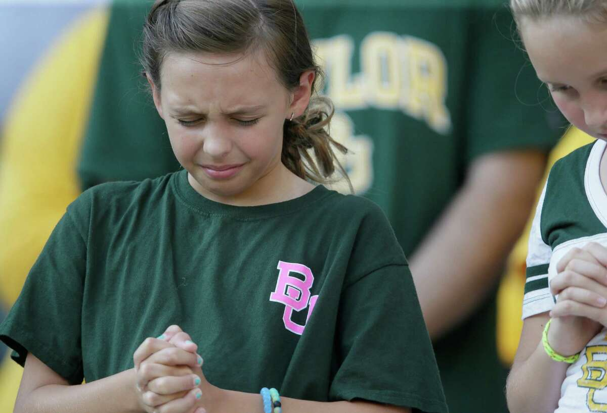 A young Baylor fans prays before an NCAA college football game between Baylor and Northwestern State Friday, Sept. 2, 2016, in Waco, Texas. (AP Photo/LM Otero)