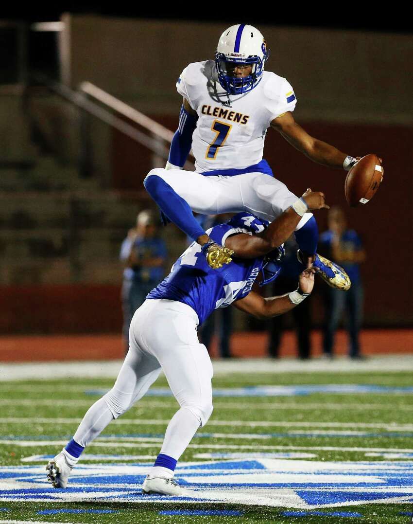 Clemens quarterback Frank Harris (07) leaps over MacArthur's K.O. Garibaldi (44) during their game at Heroes Stadium on Friday, Sept. 2, 2016. Harris scored two touchdowns in the first half.