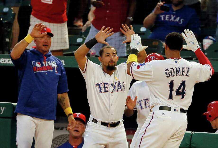 Texas Rangers' Jeff Banister, left, and Rougned Odor, center, celebrate with Carlos Gomez (14) after Gomez and Jonathan Lucroy scored on a throwing error by Houston Astros third baseman Alex Bregman during an Elvis Andrus at-bat in the second inning of a baseball game, Friday, Sept. 2, 2016, in Arlington, Texas. Andrus reached third on the error. (AP Photo/Tony Gutierrez) Photo: Tony Gutierrez, Associated Press / Copyright 2016 The Associated Press. All rights reserved.