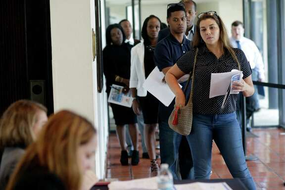 Raisa Rickie waits to  apply  for a job with Aldi at a job fair this summer in Miami Lakes, Fla. The Labor Department said Friday that in August U.S. employers added 151,000 jobs.