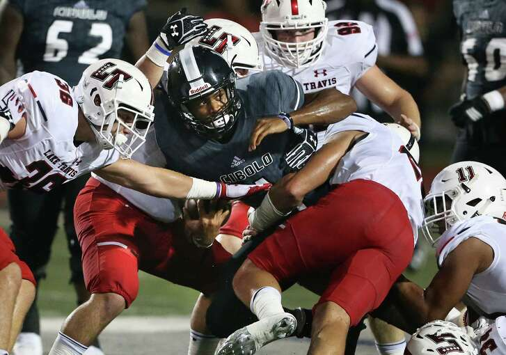 Knights quarterback Xavier Martin peers forward out of a pack of tacklers as Steele hosts Austin Lake Travis at Lehnhoff Stadium on Sept. 2, 2016.