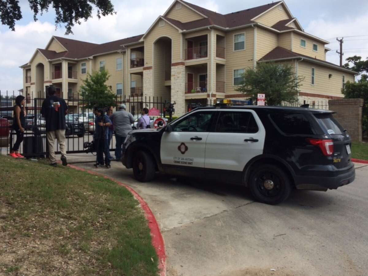 San Antonio police and onlookers gather outside an apartment at 1602 Jackson Keller Road where a 29-year-old mother of three was found stabbed to death Saturday morning.