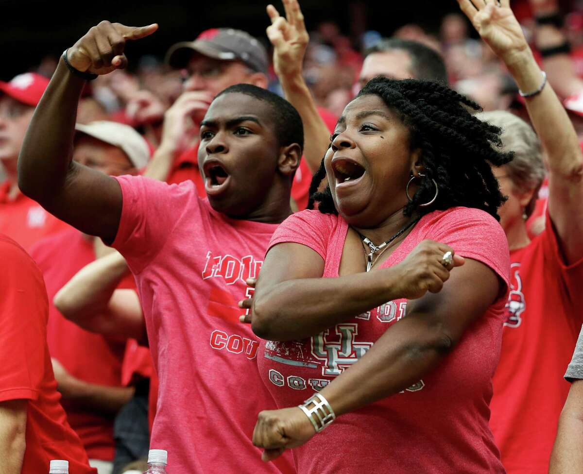 University of Houston football fans Natalie Dickson and her son Nassen Sharrieff react to a play during the second half of the Advocare Texas Kickoff Game against University of Oklahoma at NRG Stadium Saturday, Sept. 3, 2016, in Houston . The Cougars won the game 33-23.