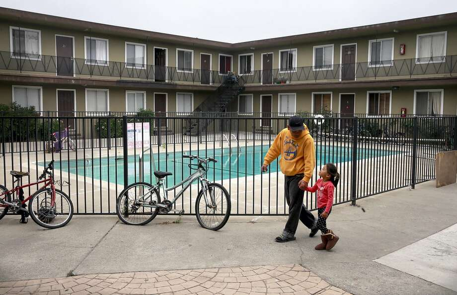 Rommel Laguardia and his 4-year-old daughter Beatrice walking across the courtyard where they have one bedroom 400 square foot Bayview apartment in Alameda, Calif. on Sat. Sept. 3, 2016. Laguardia believes his eviction to be retaliation for his activism to halt evictions in the building and plans to fight to stay in his home. Photo: Michael Macor, The Chronicle
