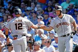 CHICAGO, IL - SEPTEMBER 03: Joe Panik #12 of the San Francisco Giants is congratulated by Madison Bumgarner #40 (R) after scoring on an RBI single by Eduardo Nunez #10 (not pictured) during the fourth inning at Wrigley Field on September 3, 2016 in Chicago, Illinois.  (Photo by Jon Durr/Getty Images)