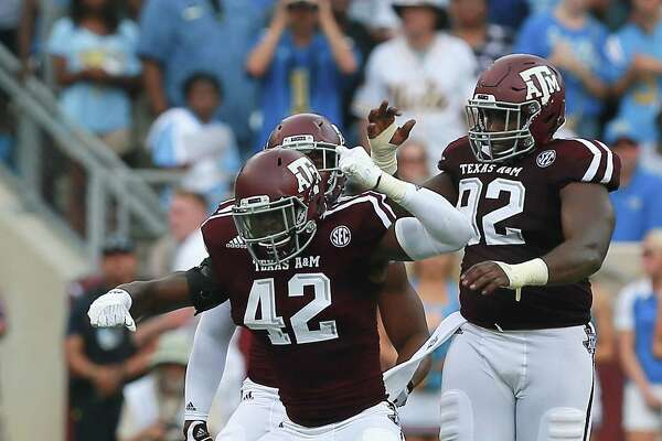 COLLEGE STATION, TX - SEPTEMBER 03:  Otaro Alaka #42 of the Texas A&M Aggies and Zaycoven Henderson #92 celebrate after a defensive stop against the UCLA Bruins at Kyle Field on September 3, 2016 in College Station, Texas.