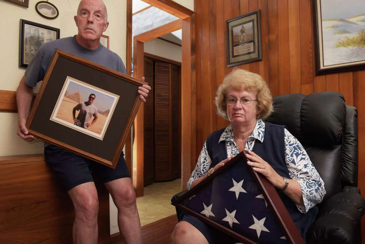 Paul Casey, left, holds a photo of his son Pat Casey as Pat's mother, Gail Casey, holds the flag which draped Pat's coffin after he died in September 2011. Photo taken on Monday, Aug. 1, 2016, at the Casey's home in Clifton Park, N.Y. (Paul Buckowski / Times Union)