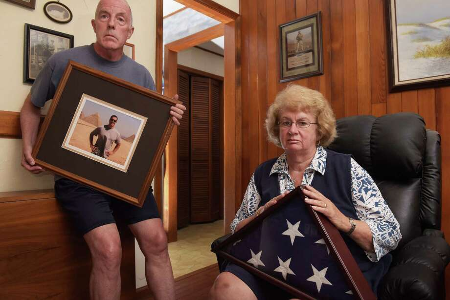 Paul Casey, left, holds a photo of his son Pat Casey as Pat's mother, Gail Casey, holds the flag which draped Pat's coffin after he died in September 2011.  Photo taken on Monday, Aug. 1, 2016, at the Casey's home in Clifton Park, N.Y.     (Paul Buckowski / Times Union) Photo: PAUL BUCKOWSKI / 20037454A