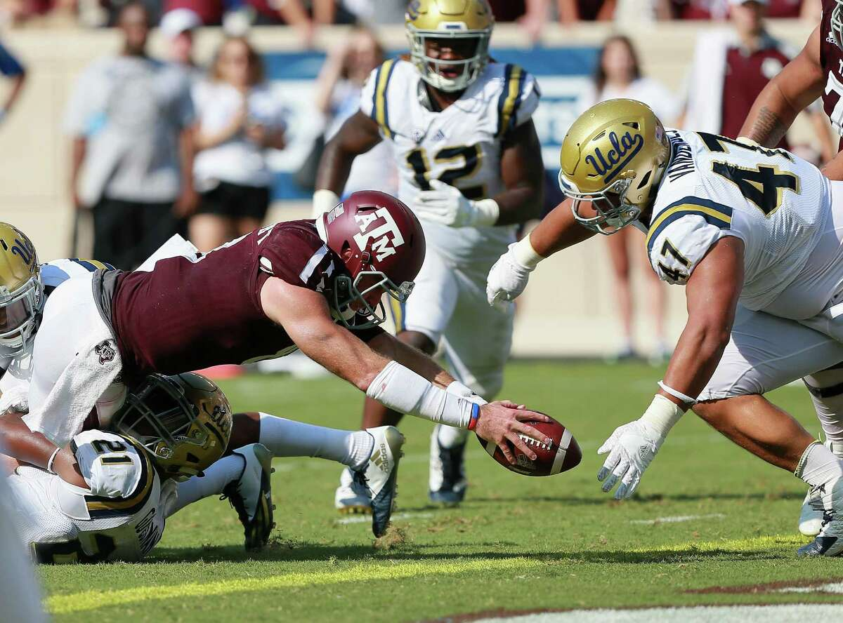 COLLEGE STATION, TX - SEPTEMBER 03: Trevor Knight #8 of the Texas A&M Aggies dives for a one yard score before Eddie Vanderdoes #47 of the UCLA Bruins or Jayon Brown can close in during the third quarter at Kyle Field on September 3, 2016 in College Station, Texas. Texas A&M won 31-24 in overtime.