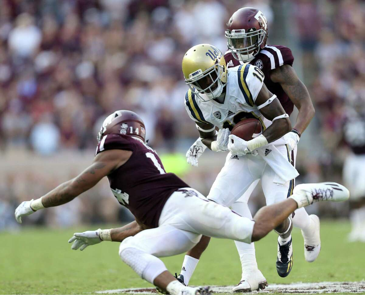UCLA wide receiver Kenneth Walker III gets away from Texas A&M's Justin Evans (14) and Nick Harvey on a touchdown reception during the fourth quarter of an NCAA college football game Saturday, Sept. 3, 2016, in College Station, Texas. Texas A&M won 31-24 in overtime. (AP Photo/Sam Craft)