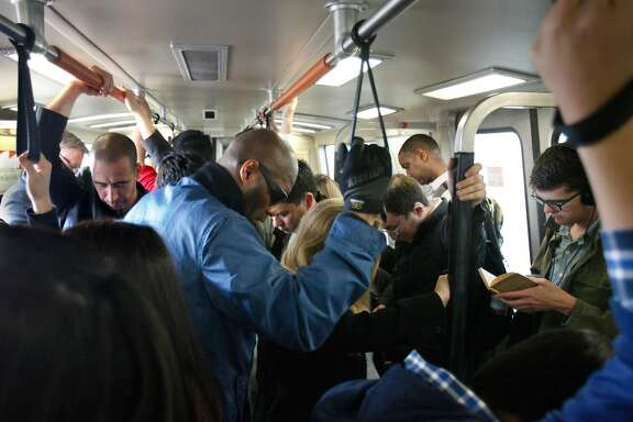 Passengers on crowded BART train hold onto hand straps as they travel through Oakland on Wednesday, April 24, 2013 in Oakland, Calif.