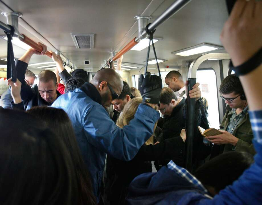 Passengers on crowded BART train hold onto hand straps as they travel through Oakland. Photo: Lea Suzuki, The Chronicle