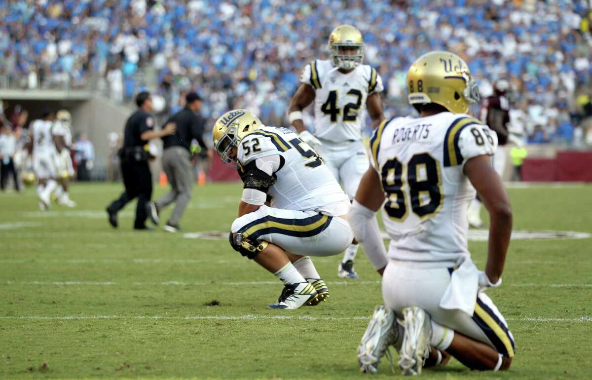 UCLA's Scott Quessenberry (52) and Takkarist McKinley (98) react after the team failed to score on fourth down in overtime against Texas A&M during an NCAA college football game Saturday, Sept. 3, 2016, in College Station, Texas. Texas A&M won 31-24 in overtime. (AP Photo/Sam Craft)