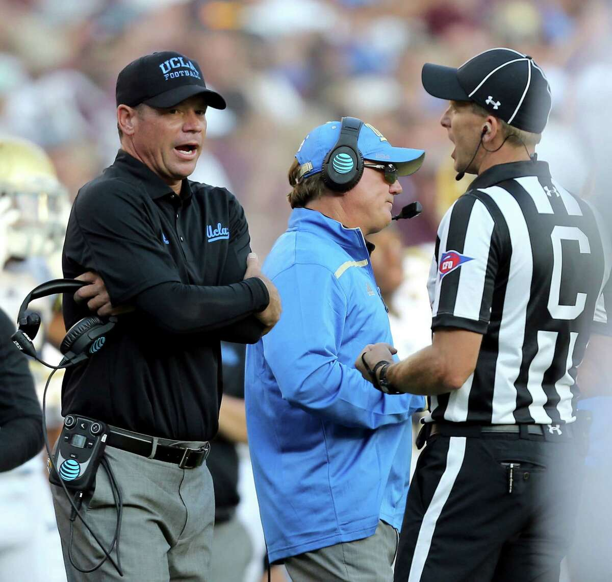 UCLA coach Jim Mora discusses a call with an official during overtime of an NCAA college football game against Texas A&M on Saturday, Sept. 3, 2016, in College Station, Texas. Texas A&M won 31-24. (AP Photo/Sam Craft)